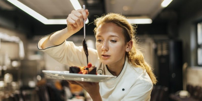 female-chef-carefully-pouring-sauce-dish_23-2148763167